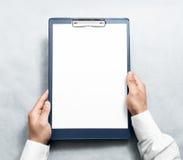 Mão que guarda a prancheta vazia com o modelo branco do projeto do papel a4 Foto de Stock