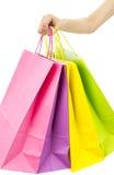 Mão que guarda sacos de compras de papel coloridos Imagens de Stock