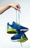 Mão que guarda tênis de corrida coloridos Imagens de Stock Royalty Free
