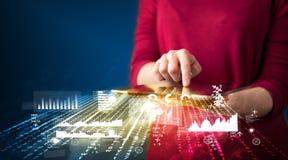 Mão que guarda a tabuleta do touchpad com gráficos do mercado empresarial Foto de Stock Royalty Free