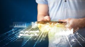 Mão que guarda a tabuleta do touchpad com gráficos do mercado empresarial Fotografia de Stock