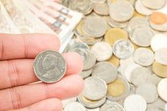 Mão que guarda Tailândia cinco moedas do baht Imagem de Stock Royalty Free
