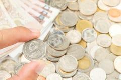 Mão que guarda Tailândia cinco moedas do baht Fotos de Stock