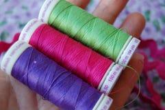 Mão que guarda três carretéis coloridos da linha em roxo, em cor-de-rosa e em verde imagem de stock
