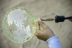 Mão que guarda um balão e para inflar com uma agulha imagens de stock