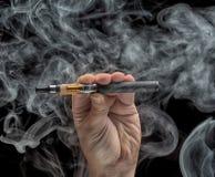 Mão que guarda um cigarro eletrônico Fotografia de Stock Royalty Free