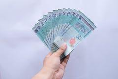 M?o que guarda um dinheiro de Mal?sia de 50 ringgits em um fundo branco imagens de stock