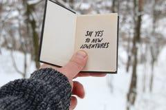 A mão que guarda um livro com a inscrição diz sim às aventuras novas no fundo da floresta do inverno fotos de stock royalty free