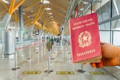Mão que guarda um passaporte italiano imediatamente antes do embarque Três linhas diferentes imagem de stock royalty free