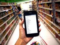 Mão que guarda um smartphone com lista do mantimento Foto de Stock