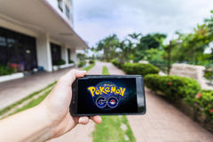 A mão que guarda um telefone celular que joga Pokemon vai imagem de stock