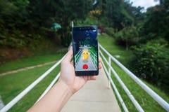 A mão que guarda um telefone celular que joga Pokemon vai Imagem de Stock Royalty Free