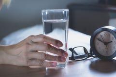 Mão que guarda um vidro da água pura Mão que prende um vidro Fotos de Stock