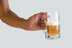 Mão que guarda um vidro da cerveja no fundo branco Foto de Stock
