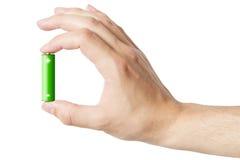 Mão que guarda uma bateria do AA, isolada Fotos de Stock Royalty Free
