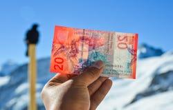 Mão que guarda uma cédula do franco 20 suíço foto de stock royalty free
