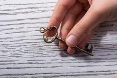 Mão que guarda uma chave decorativa denominada retro Fotos de Stock Royalty Free