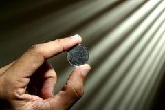 Mão que guarda uma moeda Imagens de Stock