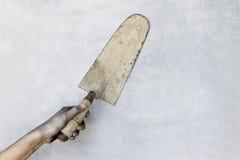 Mão que guarda uma pá de pedreiro do emplastro no fundo cinzento fotografia de stock royalty free