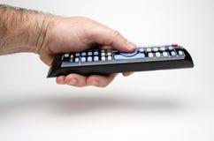 Mão que guarda a vista lateral de controle remoto Imagem de Stock