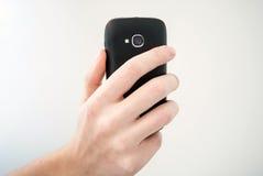 Mão que guardara o telefone móvel e que toma a foto Fotos de Stock Royalty Free