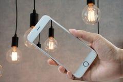 Mão que hloding o telefone esperto no bulbo Imagens de Stock Royalty Free