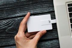 Mão que introduz a movimentação do flash de USB no portátil do computador foto de stock royalty free
