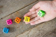 Mão que joga dados coloridos Fotos de Stock