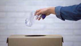 Mão que joga garrafas plásticas no escaninho de lixo, classificando o desperdício não-degradable vídeos de arquivo