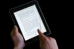 Mão que lança a página em uma tela do ipad Imagens de Stock