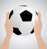 Mão que mantém a bola de futebol Fotos de Stock Royalty Free