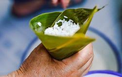 Mão que mantém a folha enchida pelo arroz pegajoso para fazer Zongzi imagens de stock royalty free