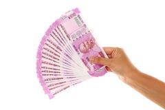 Mão que mantém 2000 notas da rupia contra o branco Foto de Stock Royalty Free