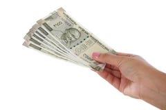 Mão que mantém notas de 500 rupias contra o branco Fotografia de Stock Royalty Free