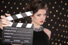 Mão que mantém o aplauso do cinema contra a mulher da forma com vermelho 'sexy' Imagens de Stock