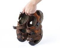 Mão que mantém a sandália velha isolada Fotos de Stock Royalty Free