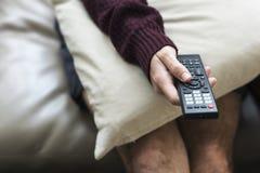 Mão que mantém a televisão de controle remoto imagens de stock royalty free