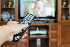 Mão que mantém a tevê de controle remoto com televisão Fotos de Stock Royalty Free