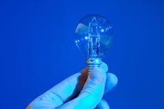 Mão que mantém um bulbo azul isolado Imagem de Stock Royalty Free
