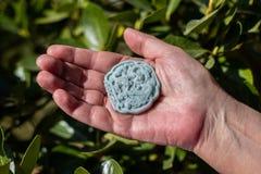 Mão que mantém uma pedra azul do jade cinzelada com testes padrões orientais com fundo verde das folhas fotografia de stock