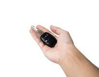 Mão que mantem chaves do carro isoladas no branco Fotos de Stock