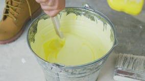 Mão que mistura a pintura amarela da parede na cubeta filme