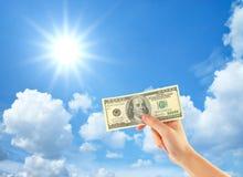 Mão que mostra o dinheiro sobre o céu imagem de stock