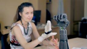 Mão que move-se, braço biônico do ` s da menina que repete seus movimentos 4K video estoque
