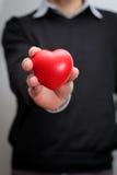 Mão que olding um coração Imagens de Stock