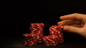 Mão que põe as microplaquetas de pôquer isoladas sobre preta, tentação para a aposta tudo, apego vídeos de arquivo