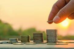Mão que põe a moeda sobre a pilha das moedas Foto de Stock Royalty Free