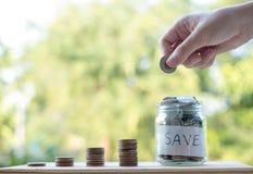 A mão que põe moedas do dinheiro empilha o crescimento, salvar o dinheiro para o conceito da finalidade imagens de stock royalty free