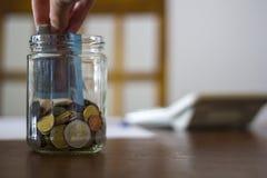 Mão que põe o dinheiro no frasco de vidro com a calculadora sobre o fundo fotos de stock