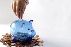 Mão que põe o dinheiro no mealheiro azul em moedas de um centavo canadenses foto de stock